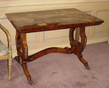 Regency rosewood writing table on lyre-end standards.