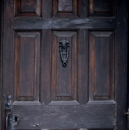 The oak front door and cast-iron door knocker at Hill Top, the home of Beatrix Potter in Sawrey, Cumbria