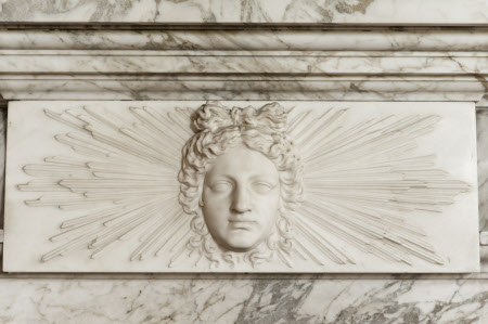 The face of Apollo on the fireplace in the Library at Wimpole Hall, Cambridgeshire.